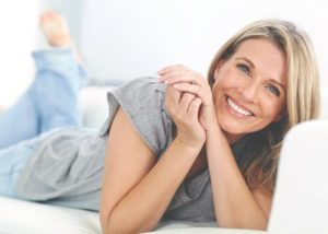 Blonde woman lying on couch smiling